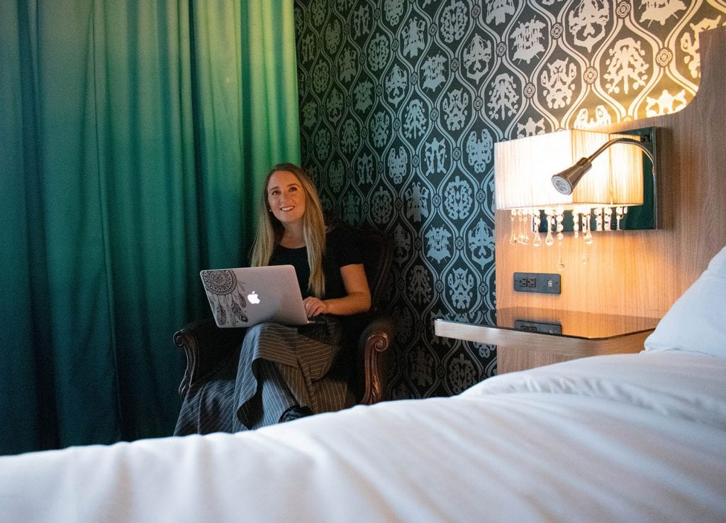 A woman working on a blogging course in a hotel room during her travels