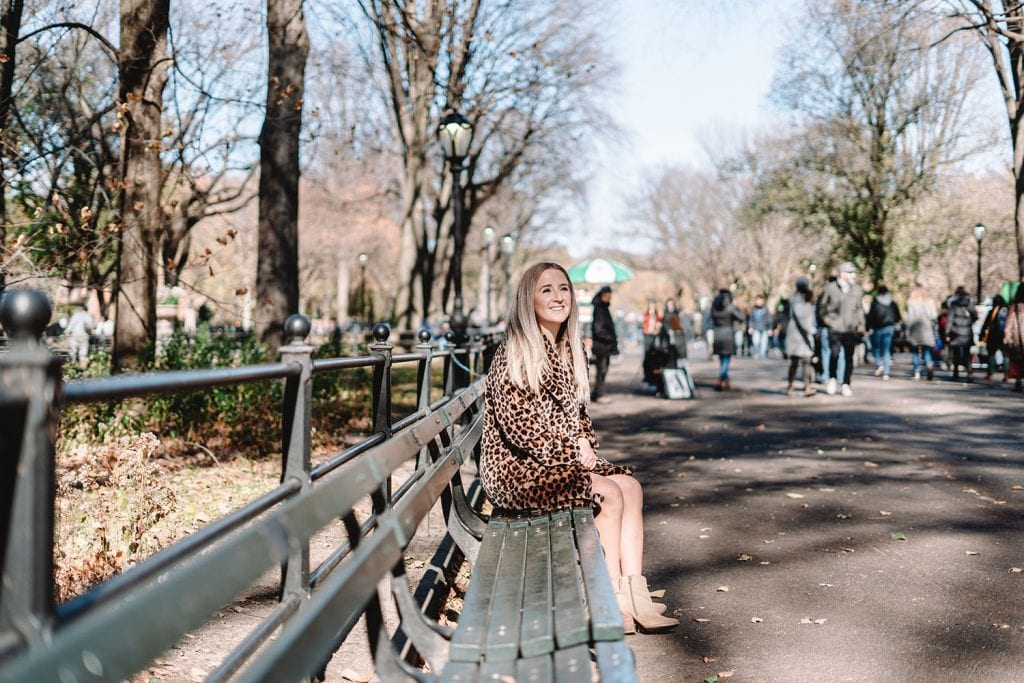 A woman sitting at a park bench at The Mall in Central Park, NYC
