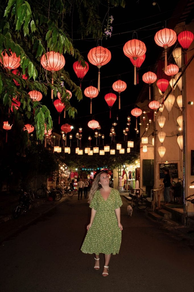 A woman walking through Hoi An Ancient Town and admiring all of the lanterns