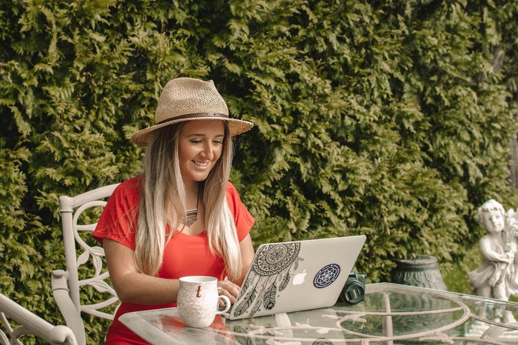 A woman working on a blogging course in her backyard