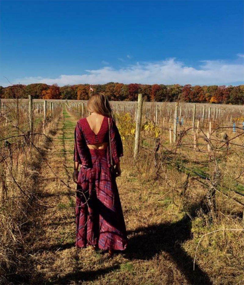 A woman walking through a vineyard
