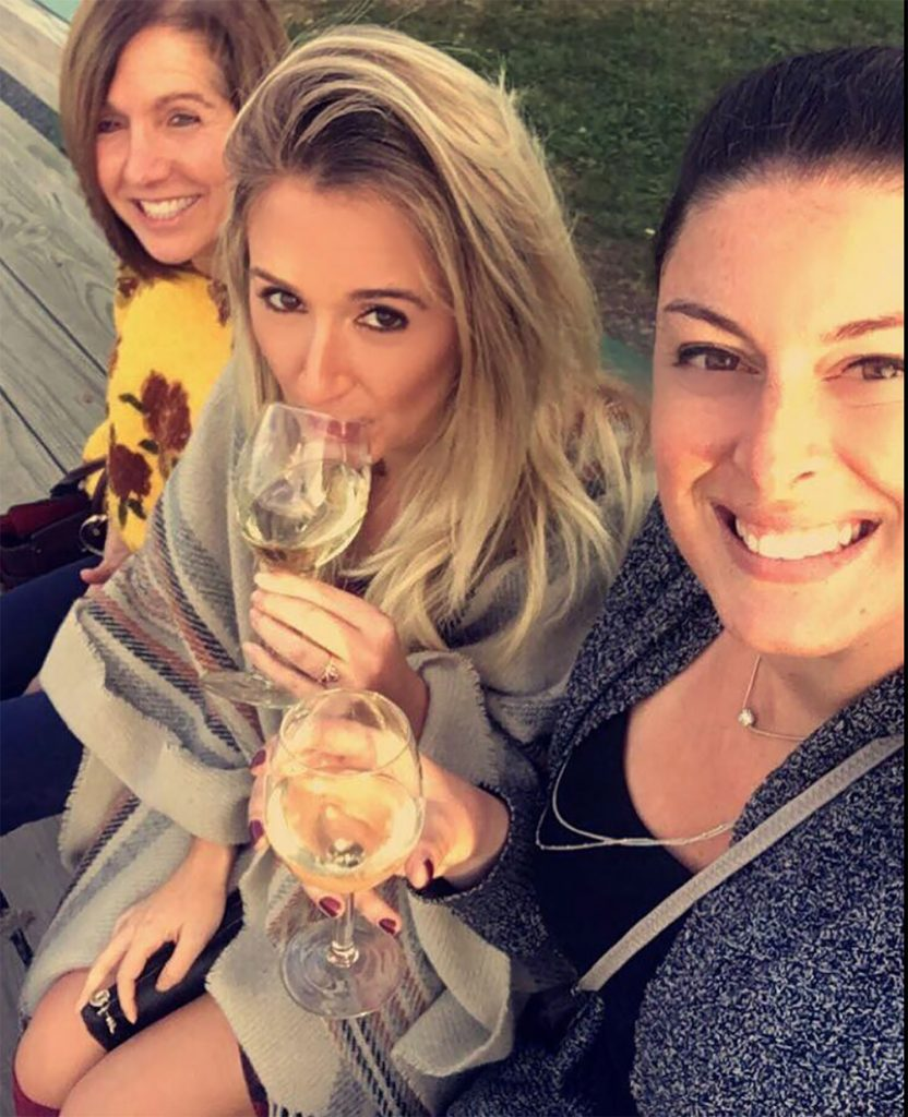 Three women on a hayride at a winery