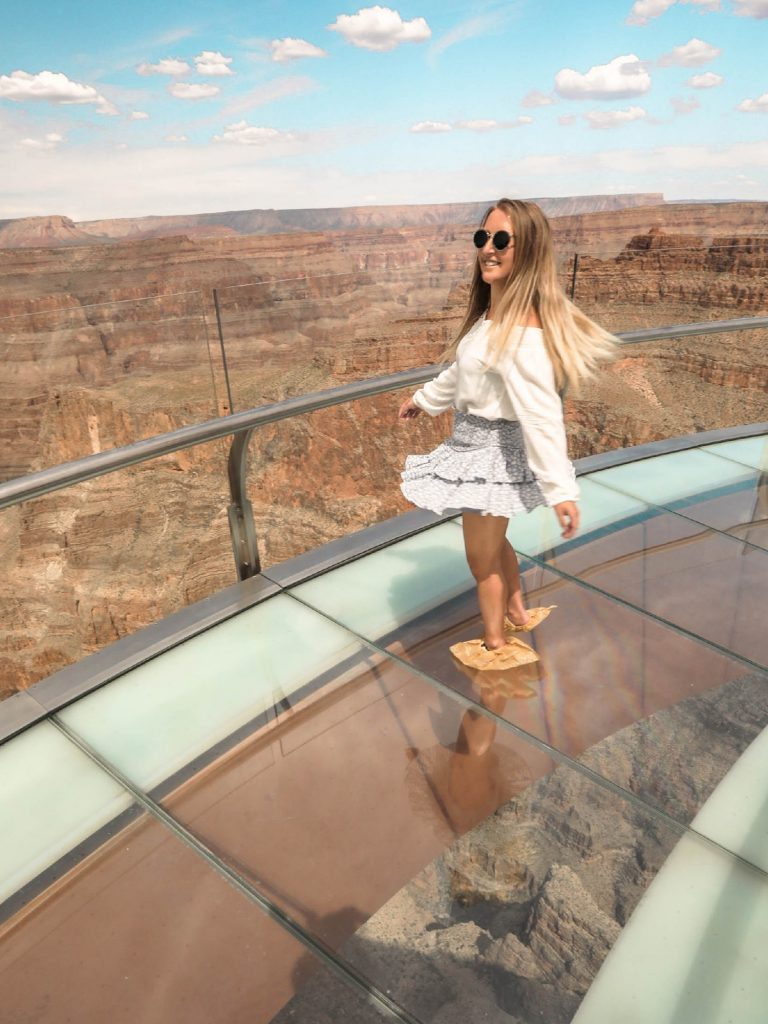 A woman twirling on the Skywalk at Grand Canyon West Rim