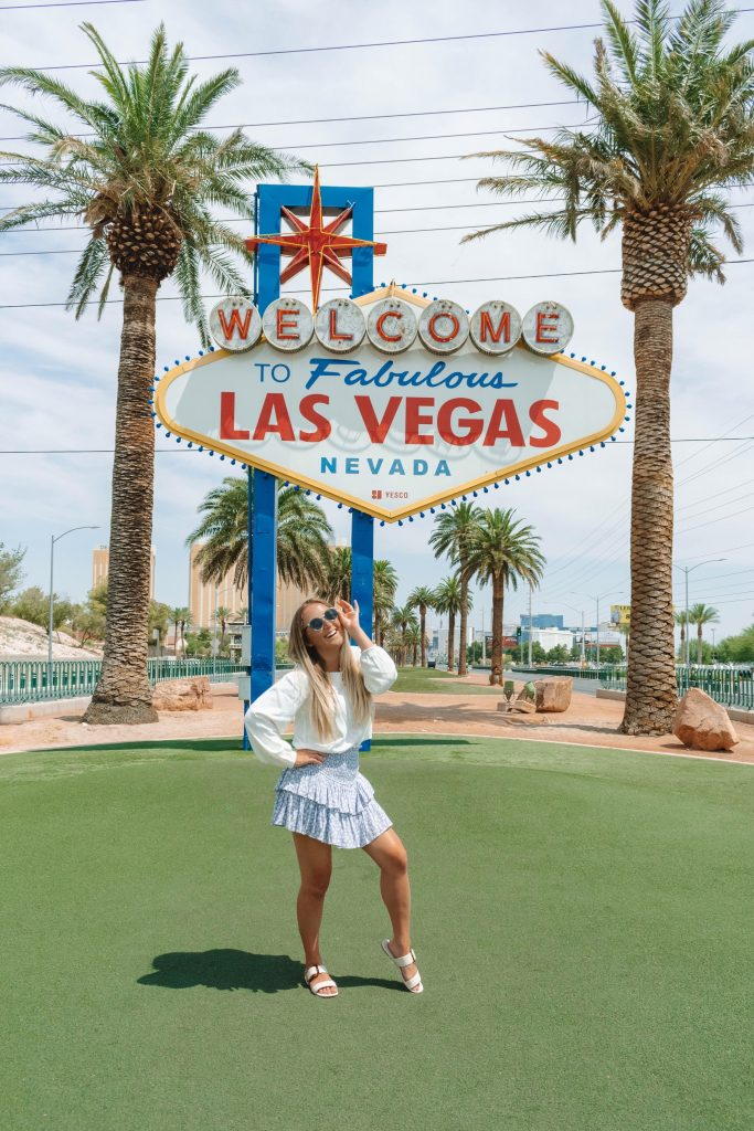 A woman having fun in front of the Welcome to Las Vegas Sign