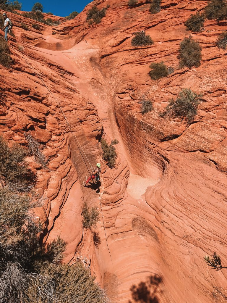 A woman repelling down a canyon in Zion National Park