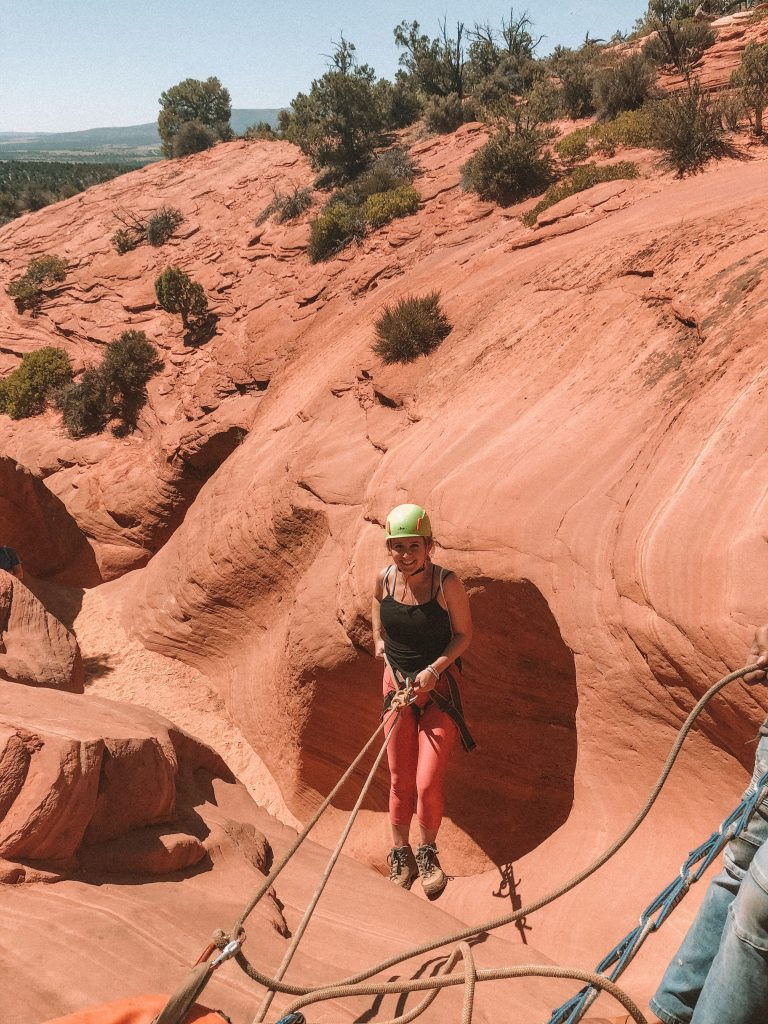 A woman getting ready to repel down a slot canyon