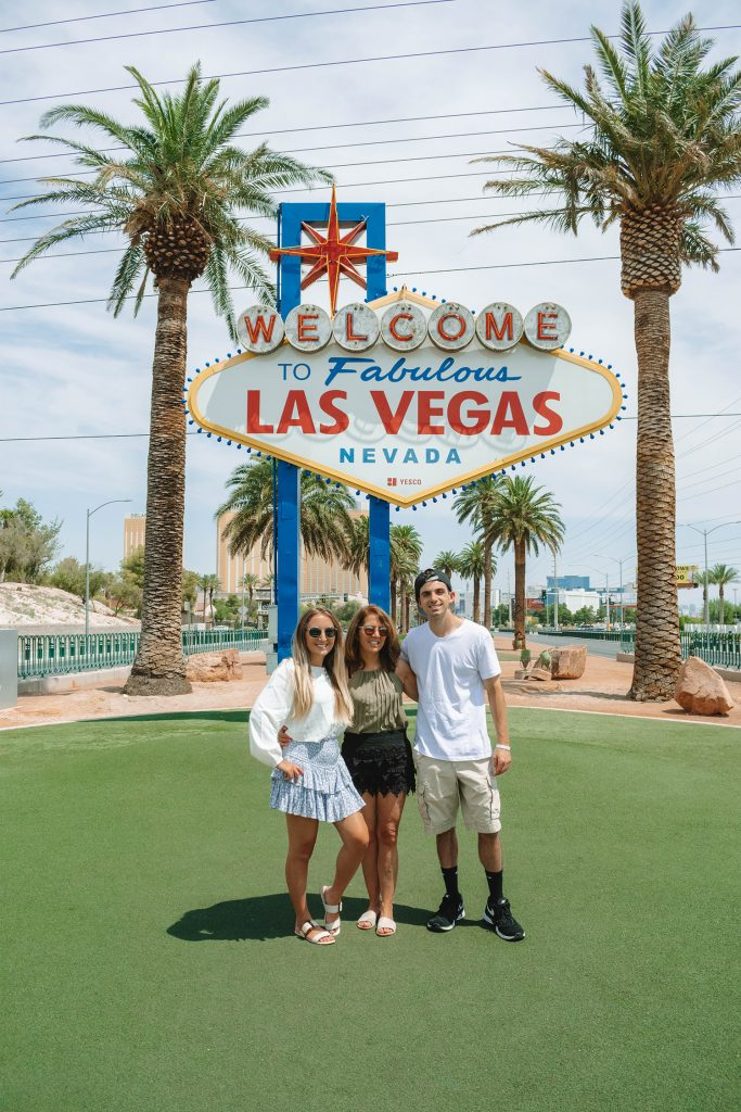 A family in front of the iconic Las Vegas Sign