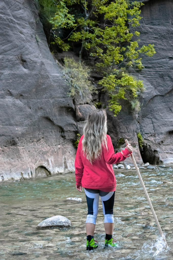 A woman hiking The Narrows at Zion National Park