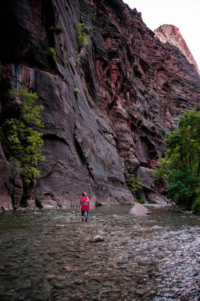 A woman hiking The Narrows in Zion National Park