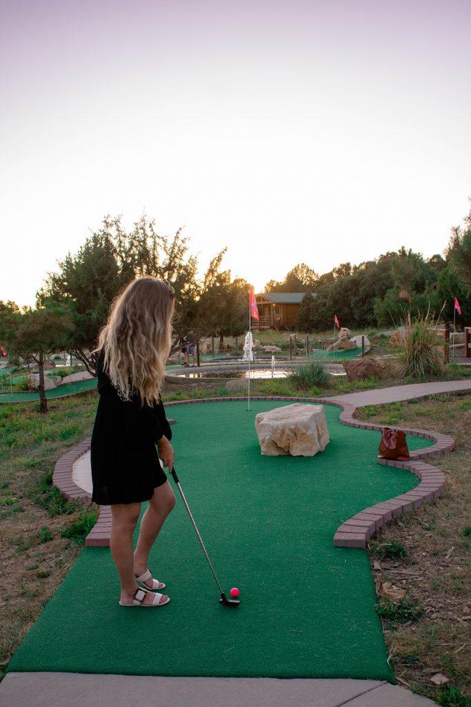 A woman mini golfing at Zion Ponderosa