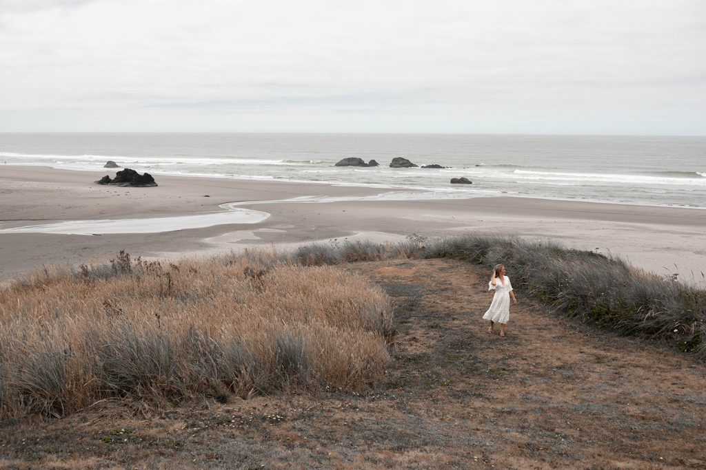 A woman walking the beach on a Northern California and Oregon road trip