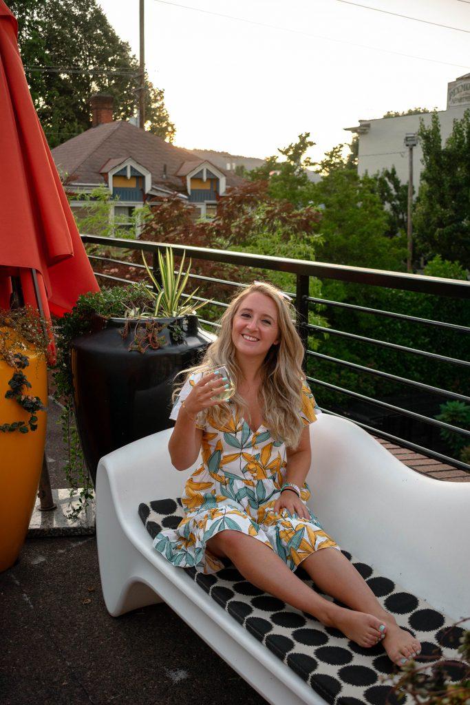A woman drinking wine on a rooftop in Portland, Oregon