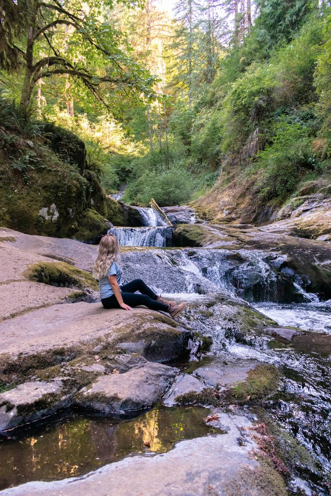 A woman admiring Sweet Creek Falls in Oregon