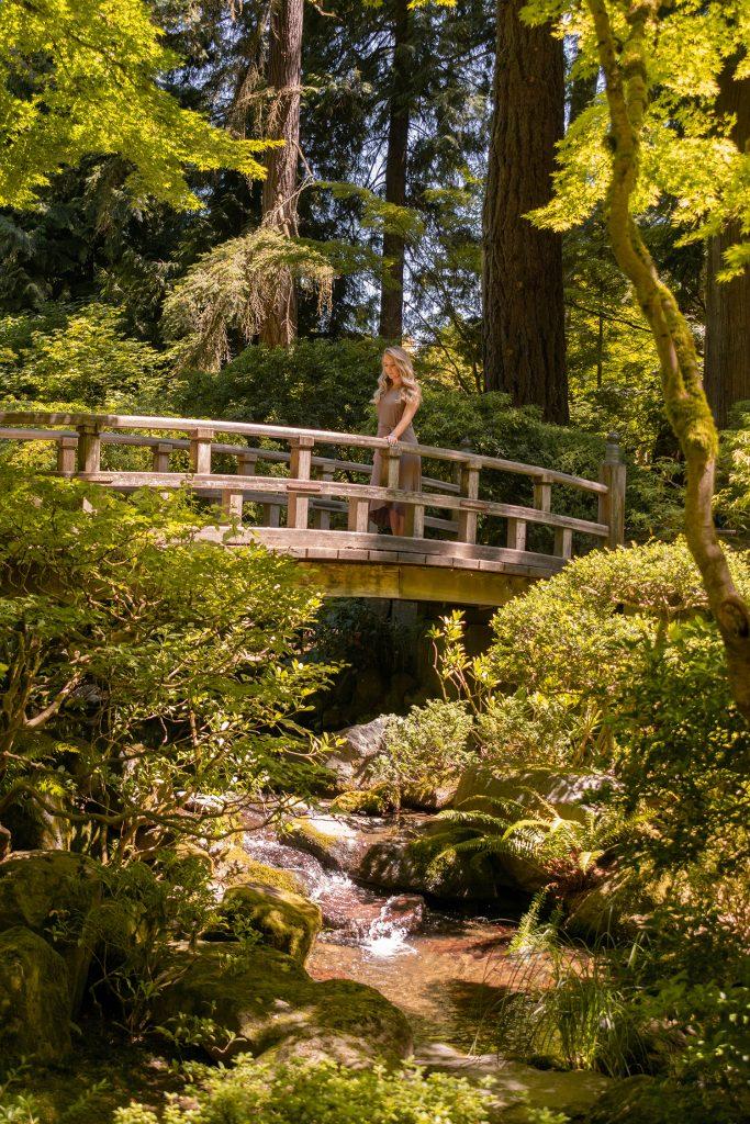A woman on a traditional bridge at the Portland, Oregon Japanese Garden