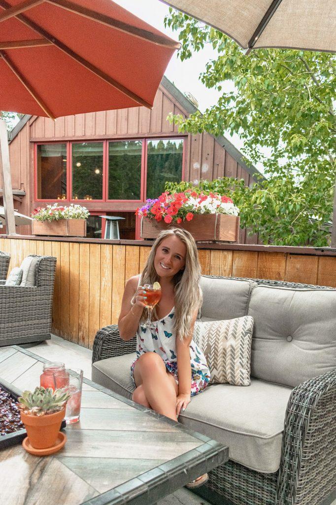 A woman enjoying a summer happy hour beverage at Lake Tahoe's Granlibakken