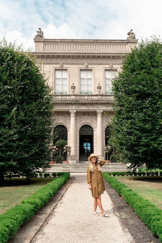 A woman standing in front of a Newport mansion
