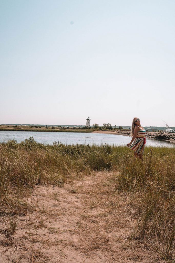A woman in front of Edgartown Harbor Light