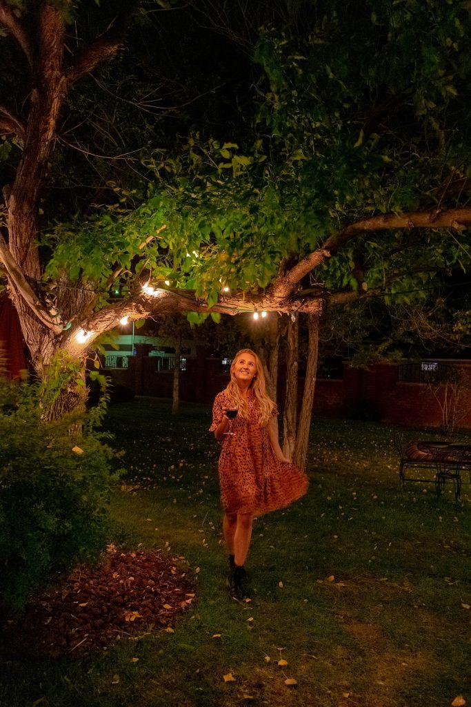 A woman walking around Chamberlin Inn's garden at night