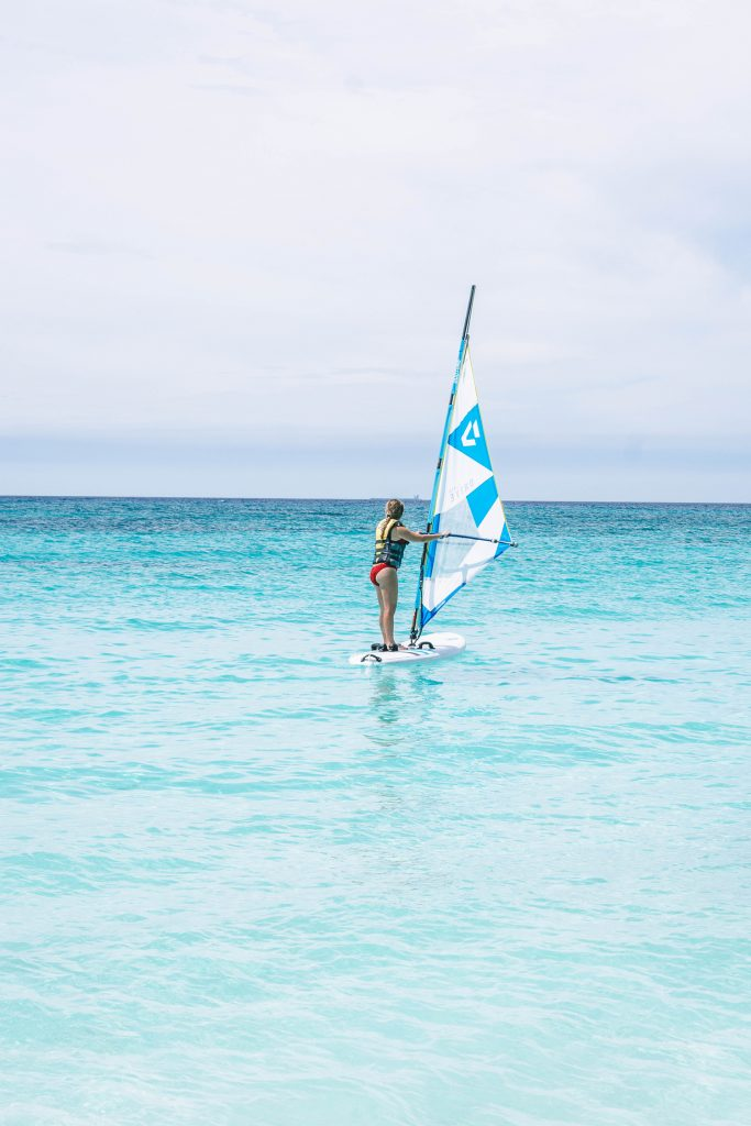 A woman learning how to wind surf at Divi All Inclusive Aruba