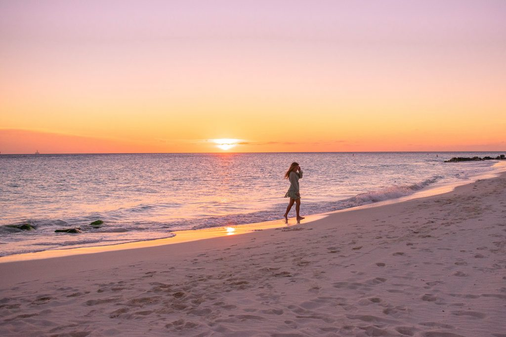 A woman walking the beach during sunset at Divi All Inclusive Aruba
