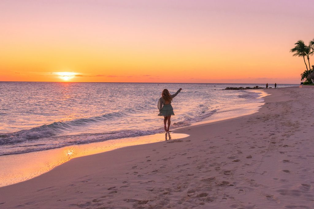 A woman twirling during a sunset in Aruba