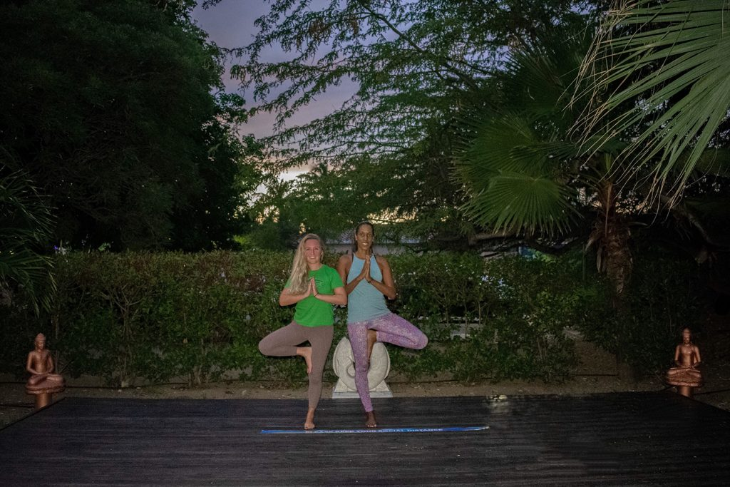Two women doing yin yoga at Divi All Inclusive Aruba