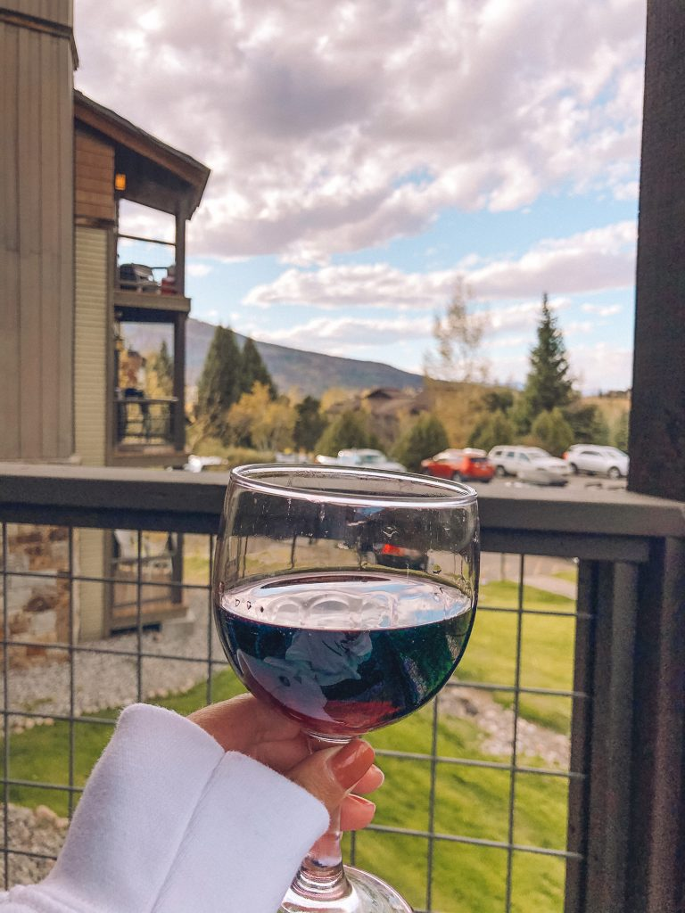 Having a glass of wine with a fall view in Steamboat Springs, Colorado