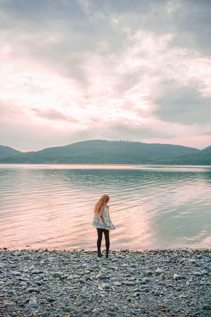 A woman at Whitefish Lake during the best Montana road trip