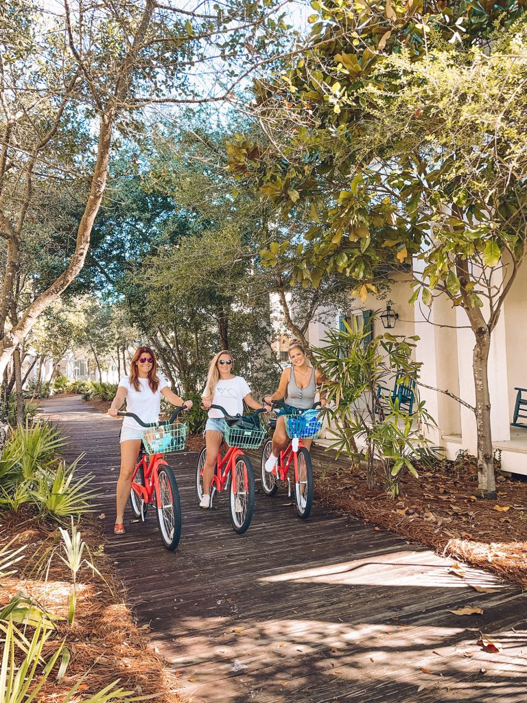 Three women enjoying a bike ride in Rosemary Beach, 30a
