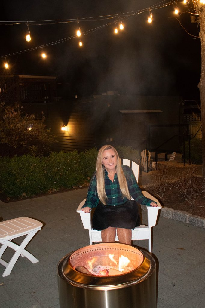 A woman sitting by a fire at Fargo Bar & Grill in Aurora, New York