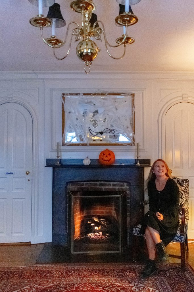 A woman warming up to a fireplace at Harbor Light in during a Halloween trip to Salem