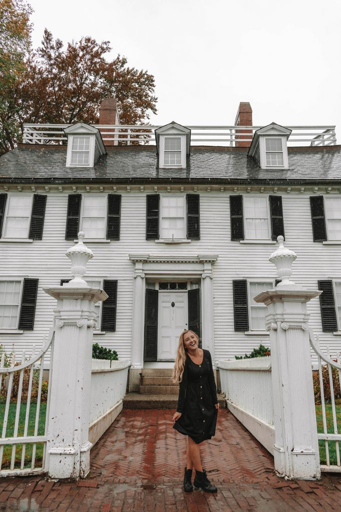 A woman standing in front of the Ropes Mansion in Salem during Halloween