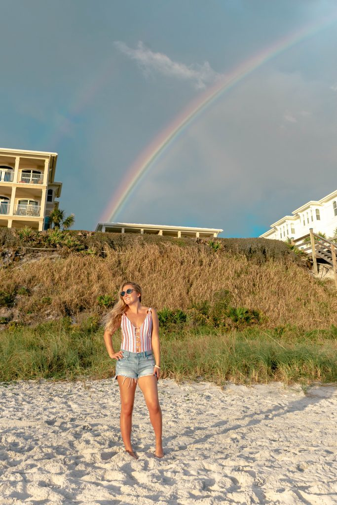 A woman enjoying a rainbow on the beach in Florida