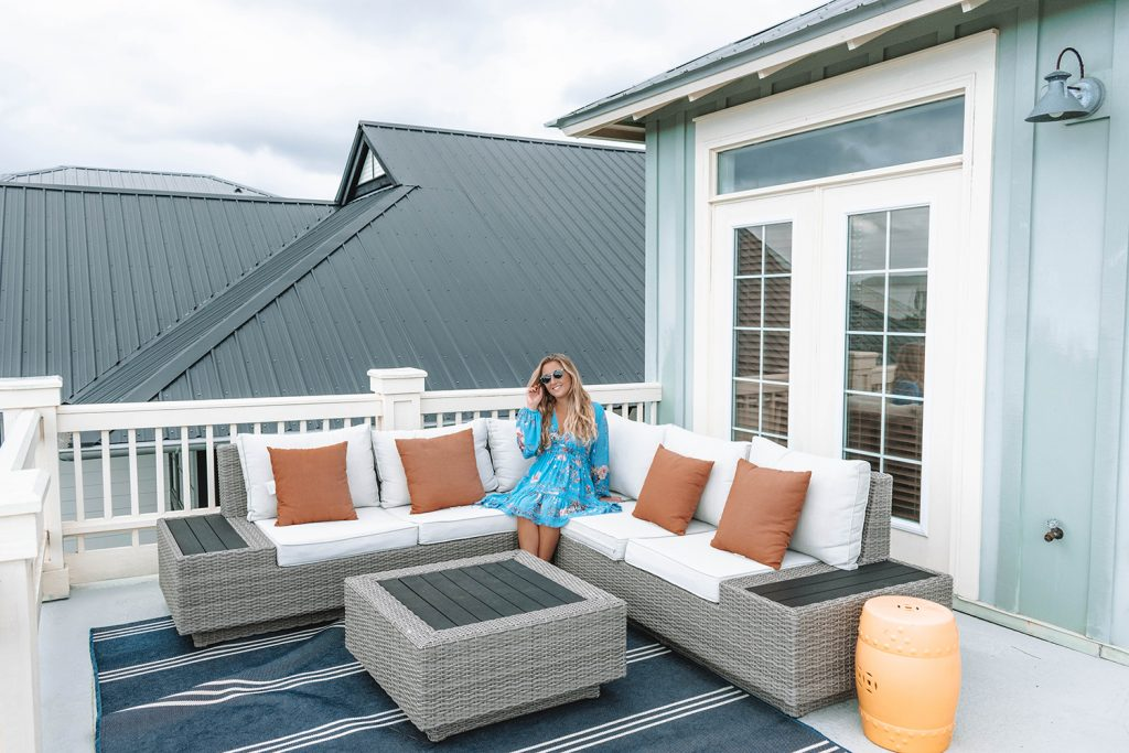A woman enjoying the 3rd floor balcony of Yourcation Awaits rental home in 30a