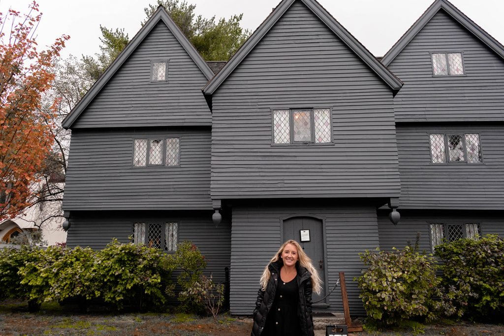 A woman in front of The Witch House in Salem during Halloween