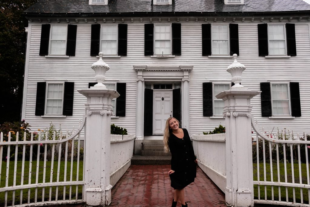 A happy woman exploring the homes in Salem during Halloween