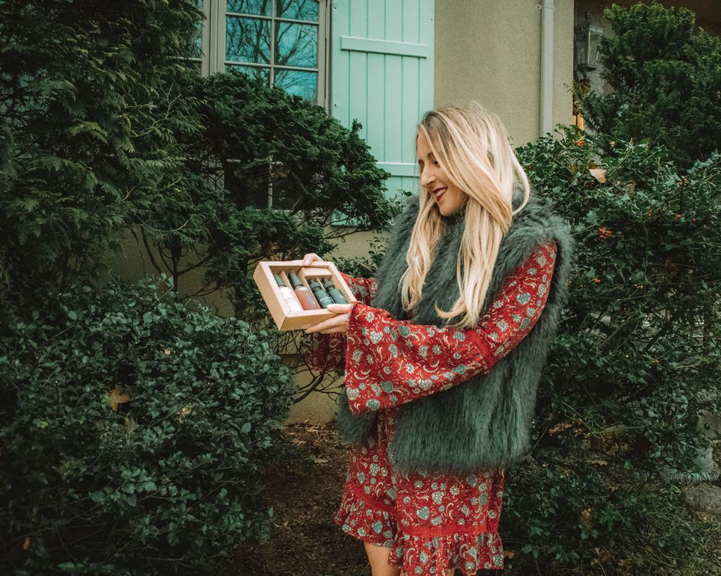 Skin Care Holiday Gift Guide - a woman holding a box of facial serums and creams