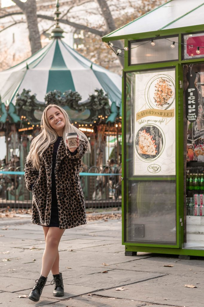 A woman enjoying a hot Christmas drink at Bryant Park's Winter Village - one of the top 40 things to do in NYC