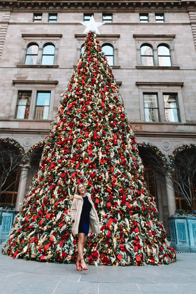 A woman in front of the Christmas tree at Lotte New York Palace - one of the top 40 things to do in NYC