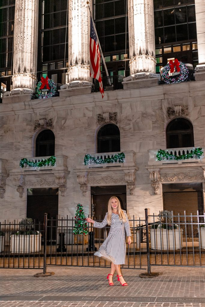 A woman enjoying the holiday decorations at the New York Stock Exchange - one of the top 40 things to do in NYC