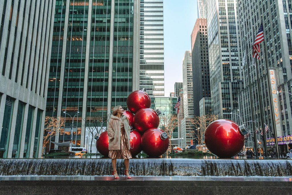 A woman standing in front of the red ornaments on 6th Avenue - one of the top 40 things to do in NYC