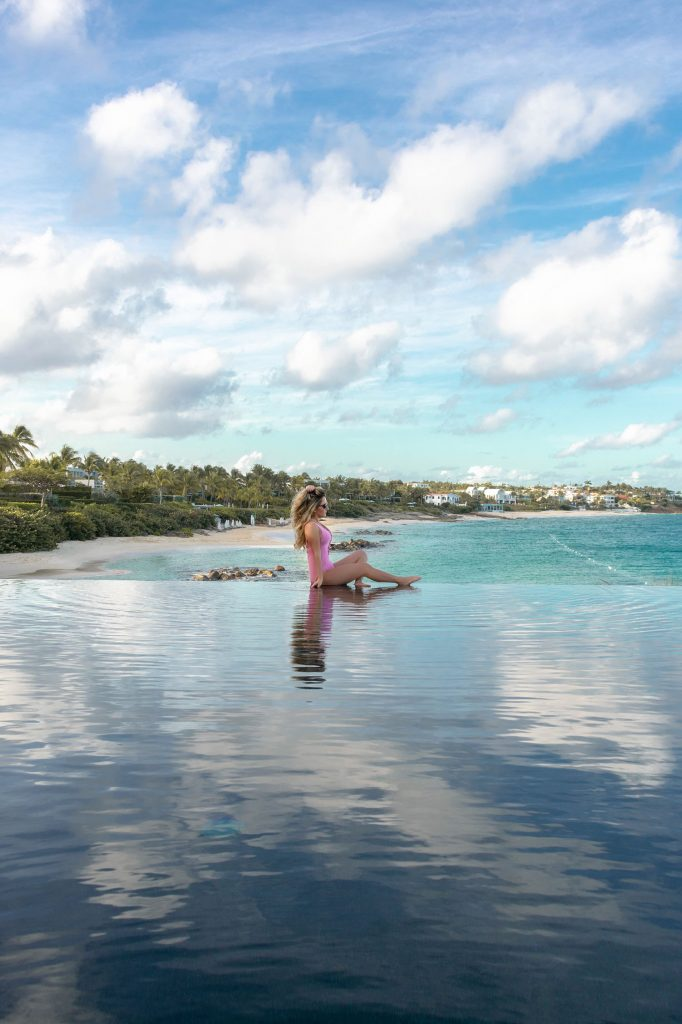 A woman sitting at the edge of an infinity pool at the Four Seasons Anguilla