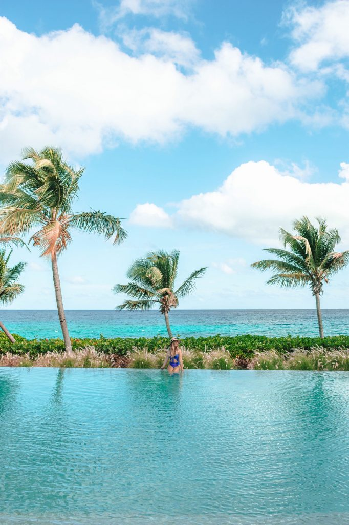 A woman sitting at the Bamboo Pool at Four Seasons Anguilla - the best luxury beach resort