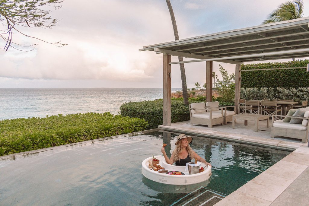 A woman sitting in a pool with a floating breakfast at the best luxury beach resort in Anguilla