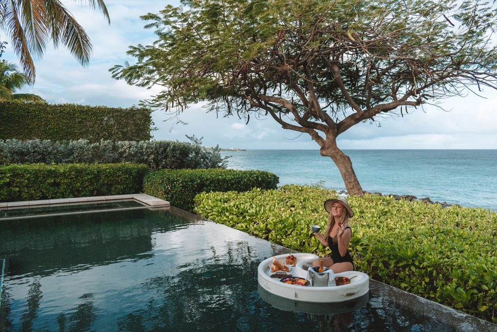 A woman having a coffee and fresh fruit in her pool at the best luxury beach resort in Anguilla