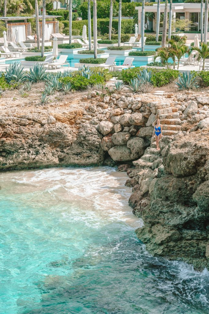 A woman standing on the cliffs near a cove at Four Seasons Anguilla - the best luxury beach resort