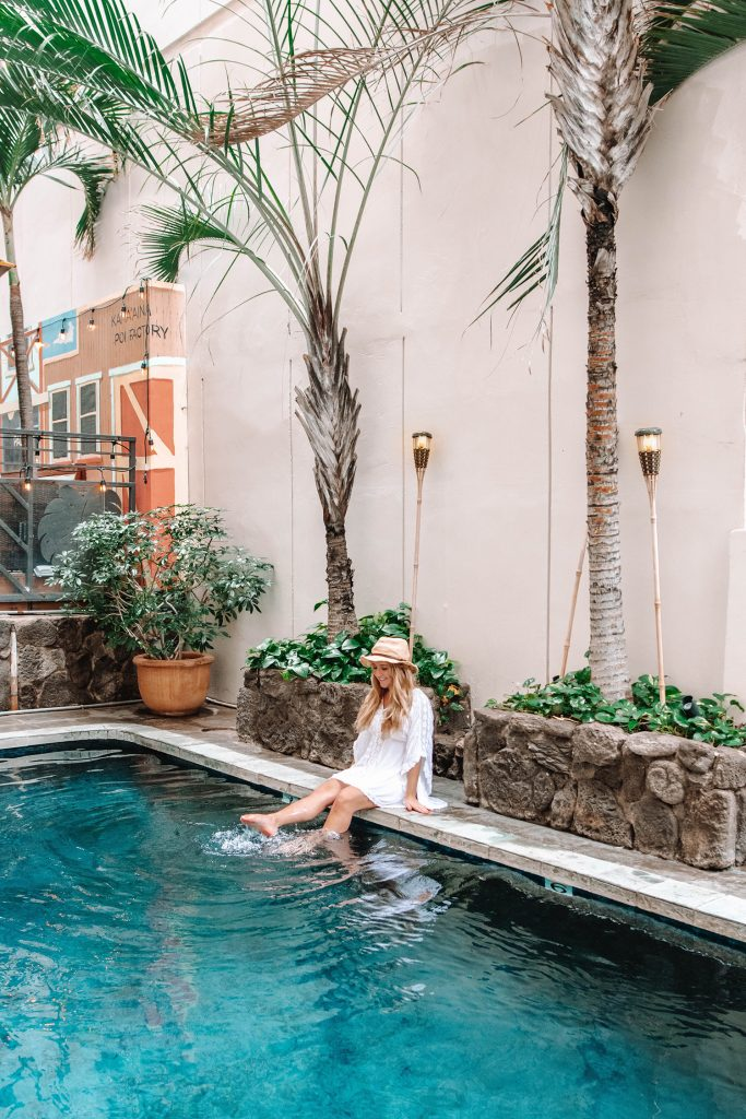 A woman enjoying the pool at The Equus Hotel in Waikiki - one of the top things to do on Oahu