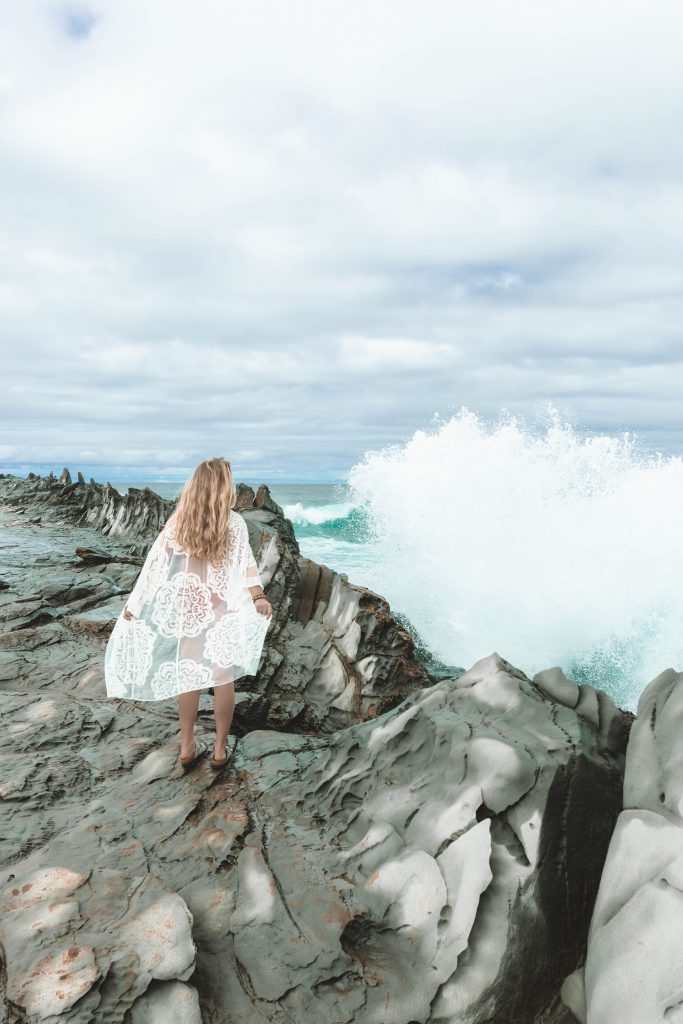 A woman enjoying the waves at Dragon's Teeth, which is part of a 10 day Oahu and Maui itinerary