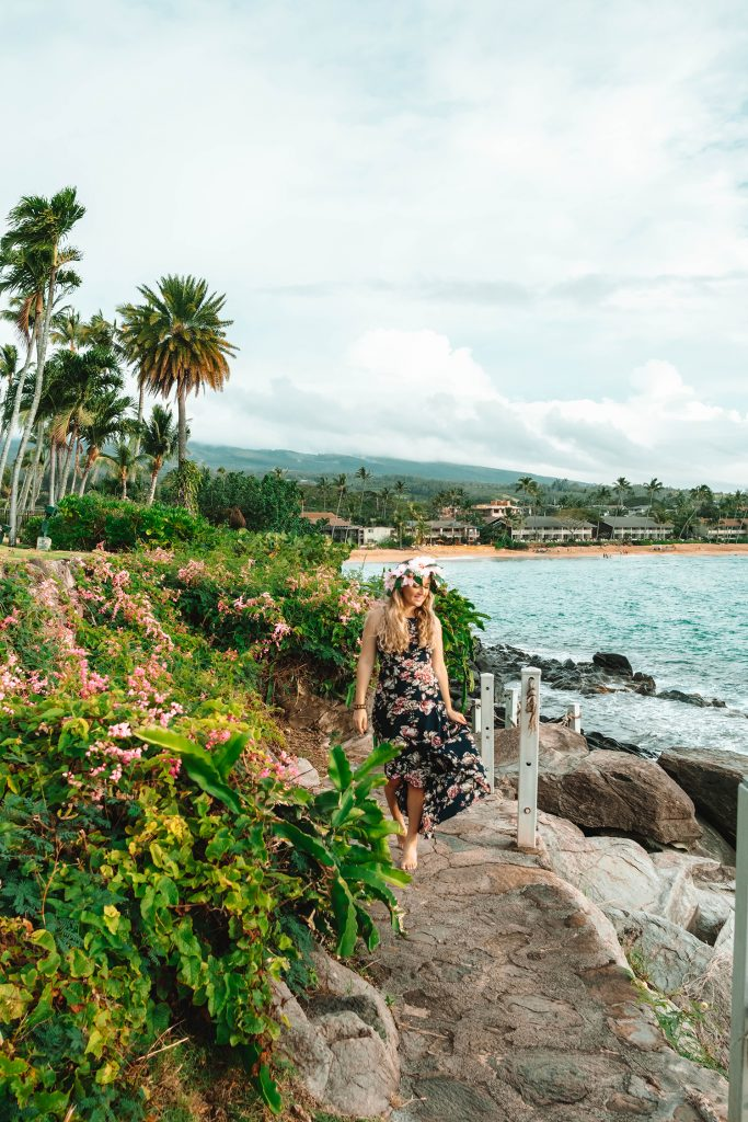 A woman walking the cliff walk at Napili Kai Beach Resort in West Maui