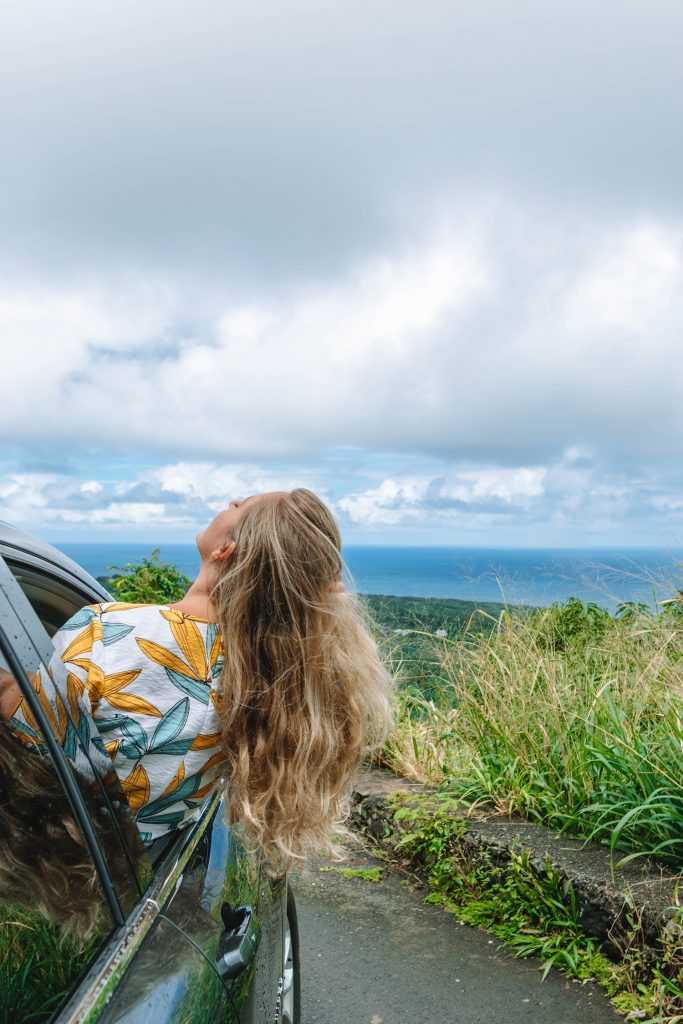 A woman enjoying the views of the Pacific Ocean on Road to Hana in Maui